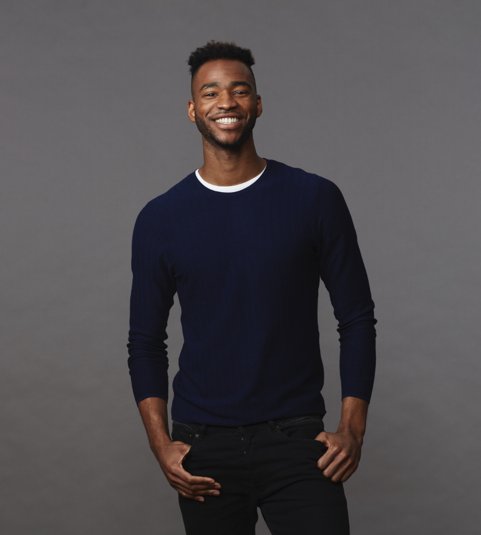 young man wearing blue smiling directly at camera on a gray studio background