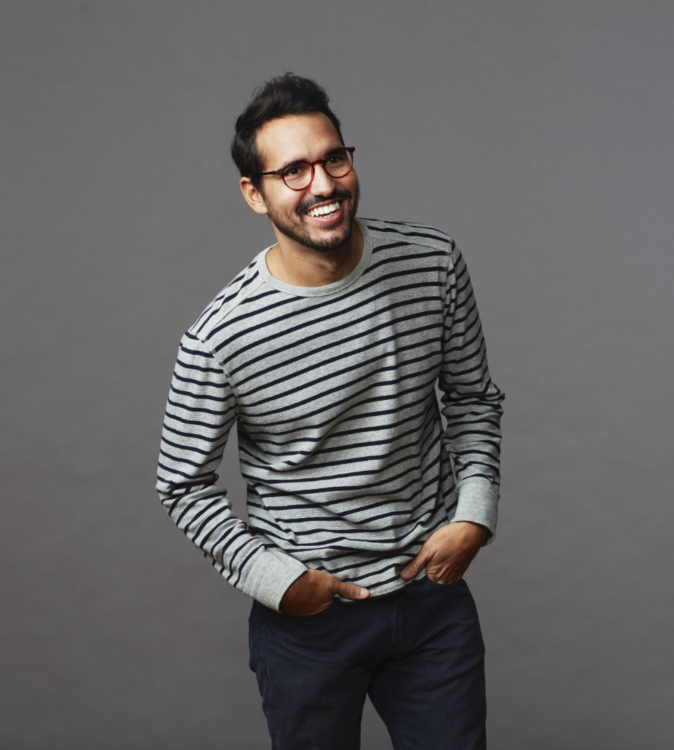 young man leaned over smiling off camera on a gray studio background