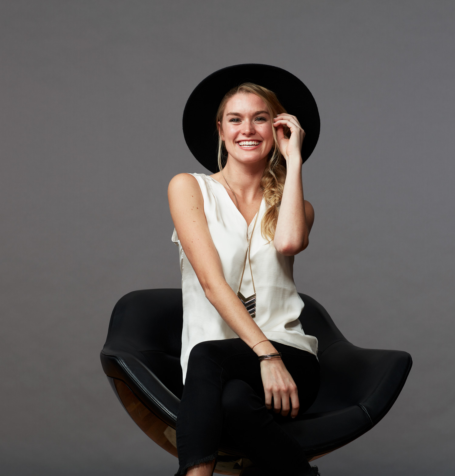 image of woman sitting in a chair in a studio smiling at the camera