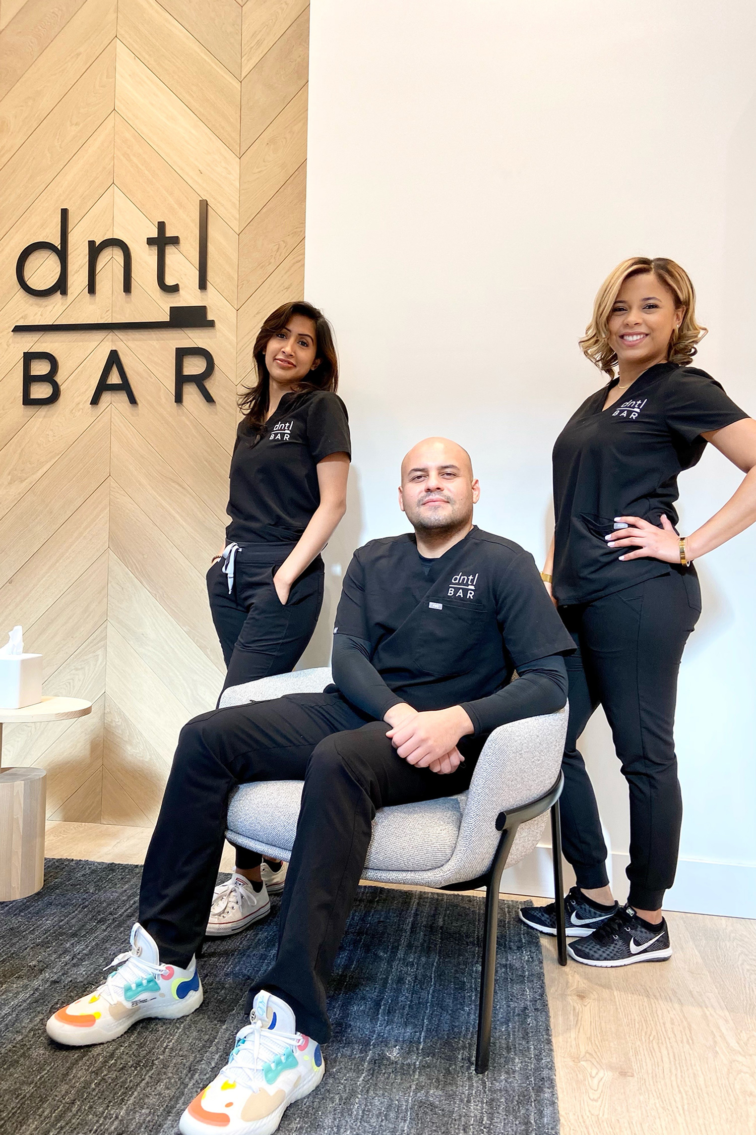 dntl bar employees in the lobby facing the camera. 1 employee is sitting and 2 employees are standing behind him.